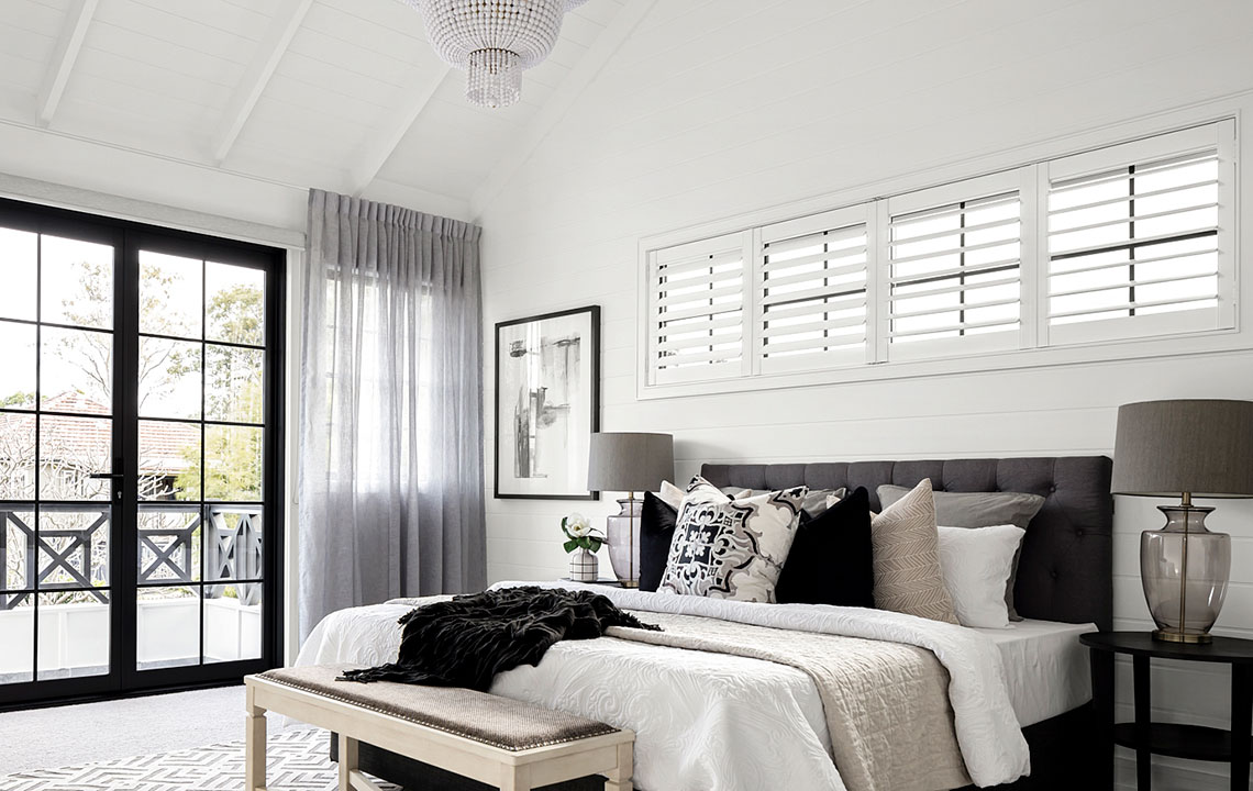 polyshield plantation shutters above a bed
