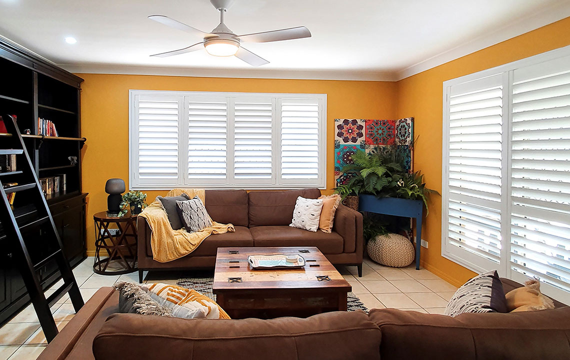plantation shutters in white against a yellow wall